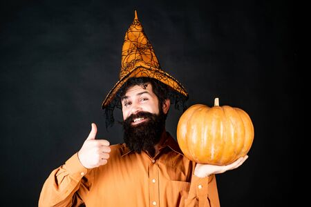 Happy Halloween - handsome man isolated. Happy Halloween. Smiling happy man with pumpkin. Young man with witch hat ready to Halloween party. Trick or treat. Archivio Fotografico - 129640702