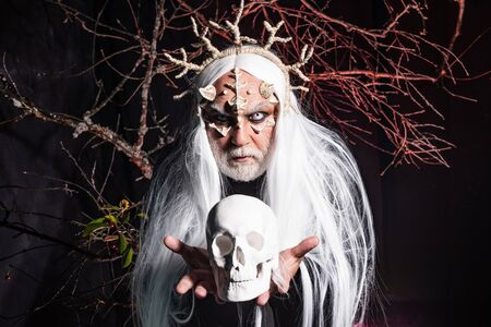 Satan on Hell. Horror with scary Halloween man. Alien with dragon skin and grey beard. Demon with bloody horns on head. Elderly man holding two red horns. Dracula - Halloween concept. Devil horns.