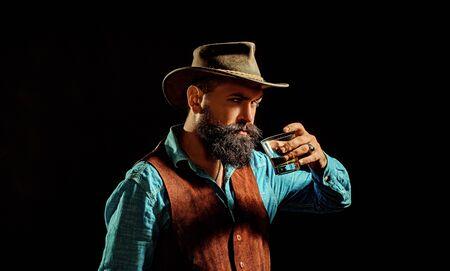 Old traditional whiskey drink - gentlemen beverage. Stylish elegant bearded man Bartender holds whiskey glass. Stylish rich man holding a glass of old whisky.