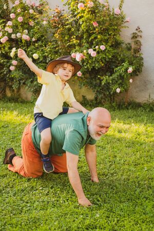 Fathers day. Grandfather and grandson Playing - Family Time Together. Child with Grandfather dreams in summer in nature. Senior man with grandson jogging in park. Grandfather and son. Stock Photo