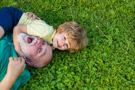 Hug and embrace - grandfather and grandson. Happy child with Grandfather playing outdoors. Stock Photo