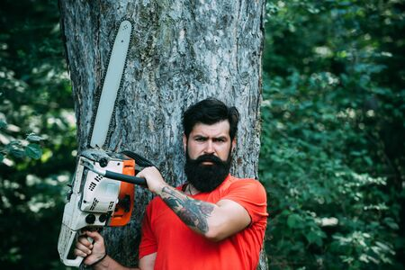 Woodcutter with axe or chainsaw in the summer forest. Deforestation. Handsome young man with axe near forest. The Lumberjack working in a forest. Chainsaw. Stock Photo