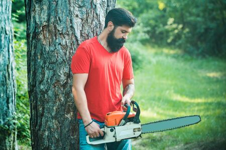 Lumberjack in the woods with chainsaw axe. Handsome young man with axe near forest. Lumberjack with chainsaw on forest background. Lumberjack holding the chainsaw.