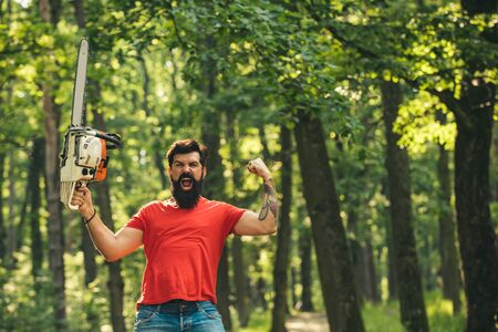 Woodcutter with axe or chainsaw in the summer forest. Lumberjack worker standing in the forest with chainsaw.