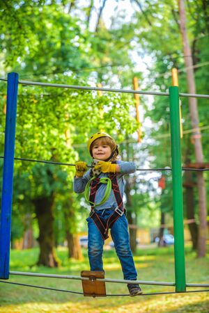 Child boy having fun at adventure park. Happy child climbing in the trees. Cute child boy. Portrait of a beautiful kid on a rope park among trees. Child.