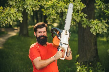 The Lumberjack working in a forest. Professional lumberjack holding chainsaw in the forest.