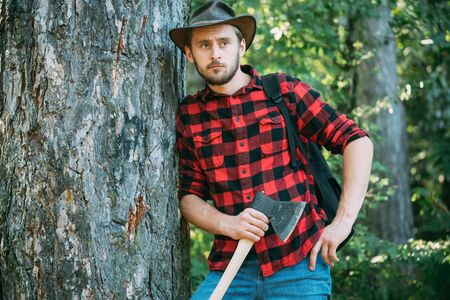 Handsome man with axe. Handsome man lumberjack with a large ax examines the tree before felling. Strong man lumberjack with an ax in a plaid shirt.