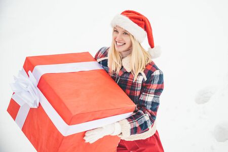 Santa woman holds a big gift box with copy space for your text. Christmas Girl holding a big gift. Big gift box. Crazy Christmas girl pushes a big gift on snow winter background. Stockfoto