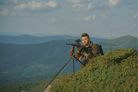 Mountain hunting. Hunter man. Hunter with shotgun gun after a hunt. Hunter with Powerful Rifle with Scope Spotting Animals. American hunting rifles.