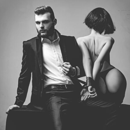 Tease and seduce. Sexy girl buttocks. Passionate lovers. Sex domination. Sex submission. Macho well groomed hipster and woman tied hands red ribbon. Sexual relations. Sex game