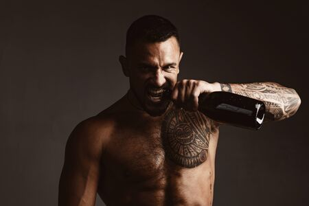Brutal handsome latinos with tattooed body opens his teeth champagne. Champagne or wine bottle. Wine celebration concept.