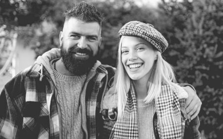 They have own style. Lumberjack style. Couple wear checkered clothes nature background. Man bearded hipster and girl wear kepi hat. Checkered style. Couple handsome bearded hipster and fashion girl