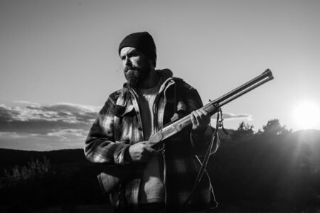 Rifle Hunter Silhouetted in Beautiful Sunset. Hunter in the fall hunting season. Hunting is the practice of killing or trapping animals.