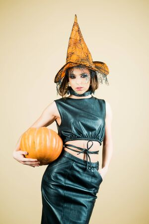 Halloween Party girl. Witch hat. Happy Halloween witch with pumpkin. Young woman with witch hat dressed as vampire for Halloween party. Stock fotó