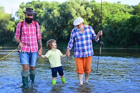 Outdoors active lifestyle. Grandfather with son and grandson having fun in river. Happy fathers day. Fishing. Summer day. Standard-Bild