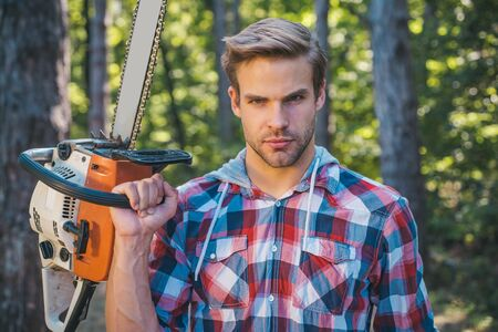 Lumberjack worker standing in the forest with chainsaw. Chainsaw. Stylish young man posing like lumberjack. Woodcutter with chainsaw on sawmill. Harvest of timber. Stock Photo
