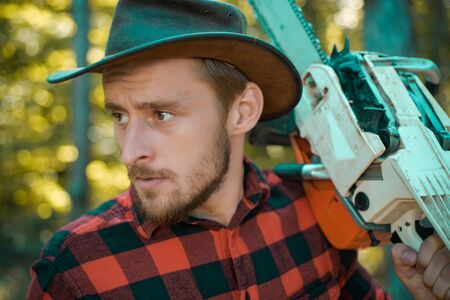 Lumberjack - close up portrait. Lumberjack with chainsaw in his hands. Woodcutter with axe or chainsaw in the summer forest. Lumberjack worker walking in the forest with chainsaw. Stock Photo