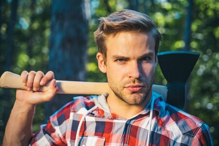 Lumberjack with ax in his hands. Handsome young man with axe near forest. Firewood as a renewable energy source. Man doing mans job. Resting after hard work. Stok Fotoğraf
