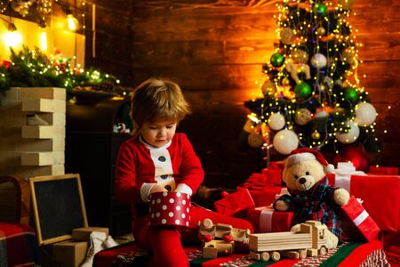 Opening gift. Santa boy little child celebrate christmas at home. Lovely baby enjoy christmas. Family holiday. Boy cute child cheerful mood play near christmas tree. Merry and bright christmas