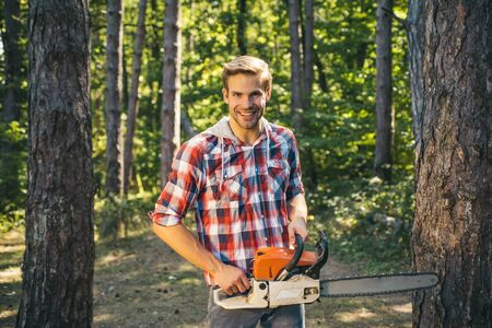Man doing mans job. Happy Woodworkers lumberjack. Lumberjack with chainsaw on forest background. Agriculture and forestry theme. Woodcutter with axe or chainsaw in the summer forest.