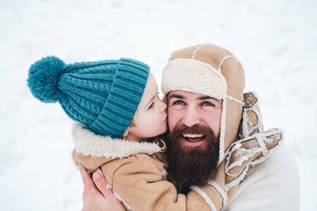 Best winter game for happy family. Happy family son hugs his dad on winter holiday. Daddy and boy smiling and hugging. Dad and baby son playing together outdoors. Father and son Having Fun in Winter Park. Zdjęcie Seryjne