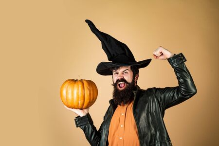 Celebrating happy Thanksgiving day. Thanksgiving day cooking. Halloween Man posing with pumpkins. Happy Halloween Weekends. Devil man. Halloween beaded man hold pumpkin - portrait. Stock Photo