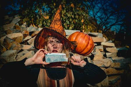 Holiday Halloween carnival costume. Halloween party art design. Beautiful young surprised woman in witch hat costume and holding Witch broom.