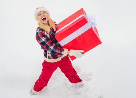 Christmas Woman holding a huge gift box. Happy winter time. Hipster Girl with Christmas gift on snow Winter landscape. Christmas winter people. Фото со стока