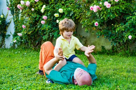 Cute child boy hugging his grandfather. Happy senior man Grandfather with cute little boy grandson playing and looking at camera. Grandfather with Son and Grandson having Fun in Park. Standard-Bild - 129970574
