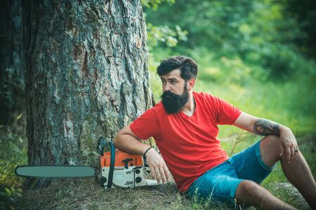 Lumberjack with chainsaw on forest background. Lumberjack with chainsaw in his hands. The Lumberjack working in a forest. Woodcutter with chainsaw on sawmill.