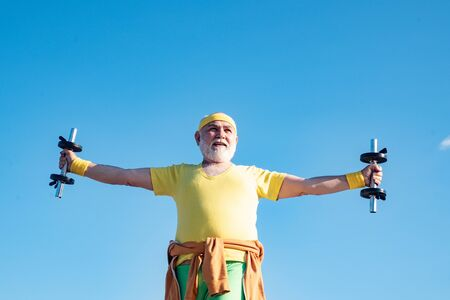 Senior man in health club. Senior fitness man training with dumbbells isolated on blue background. Senior sportman lifting dumbbells. Elderly man workout. Reklamní fotografie