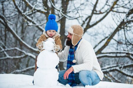 Christmas holidays. Happy winter time. Father and son making snowman.