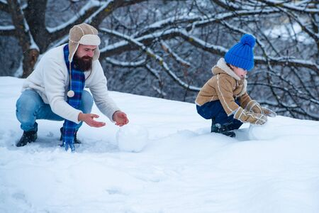 Winter game for happy family. Christmas background. Happy loving family. Father and son in snow.