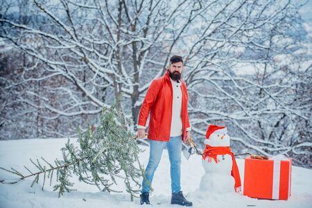 Funny Santa man posing with axe and Christmas tree. Man with beard bears home a Christmas tree. Man lumberman with Christmas tree in winter park.