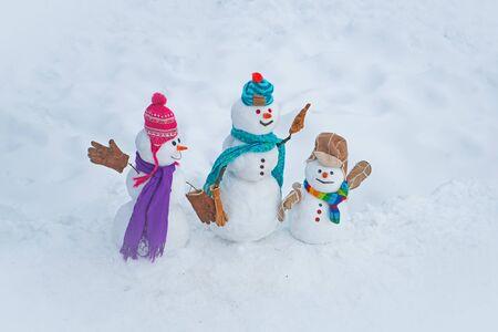 Christmas snowman on white snow background. Winter scene with snowman on white snow background. Winter background with snowflakes and snowman.