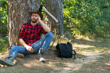 Lumberjack worker sitting in the forest. Lumberjack in the woods with an ax. Lumberjack with ax in his hands. Logging. Bearded man with axe concept. Lumberjack holding the axe.