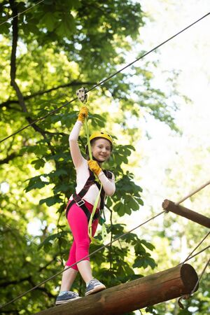 Small boy enjoy childhood years. Climber child. Helmet and safety equipment. Child concept. Adventure climbing high wire park. Kid climbing trees in park. Go Ape Adventure.