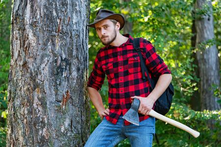 Lumberjack with ax in his hands. The Lumberjack working in a forest. Resting after hard work. Woodcutter with axe in the summer forest. Stok Fotoğraf