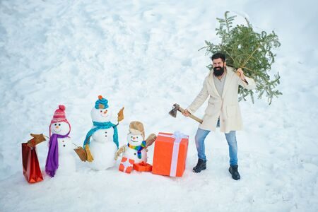 Bearded man with freshly cut down Christmas tree in forest. Man lumberman with Christmas tree in winter park. Winter portrait of lumber in snow Garden cutting Christmas tree.