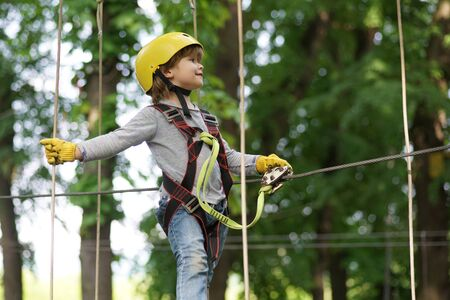 Artworks depict games at eco resort which includes flying fox or spider net. Happy little child climbing on a rope playground outdoor. Toddler kindergarten. Stock Photo