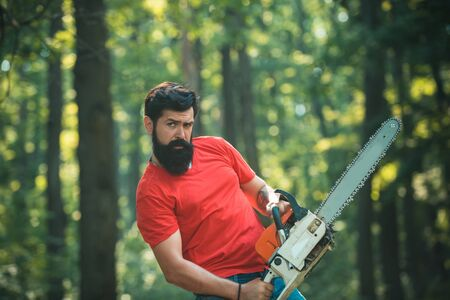 Lumberjack on serious face carries chainsaw. Agriculture and forestry theme. Lumberjack with chainsaw on forest background.