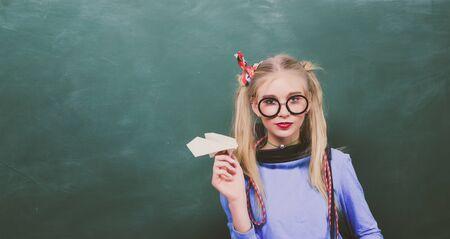 Stylish school pupil modern girl. Cute nerd funky style. Enjoying her school life. Fancy schoolgirl. School fashion. Carefree teenager. Fashionable blonde girl chalkboard background. Back to school