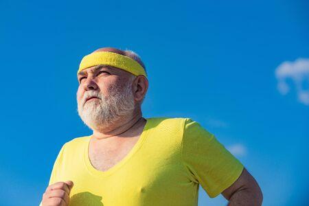 Cheerful senior jogging in sportswear on sky background. Healthy lifestyle concept. Elderly man jogging.