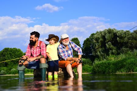 Fly fishing. Father, son and grandfather relaxing together. Coming together. Family generation and people concept. Hobby and sport activity.