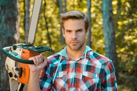 Man doing mans job. Lumberjack on serious face carries chainsaw. Deforestation is a major cause of land degradation and destabilization of natural ecosystems.