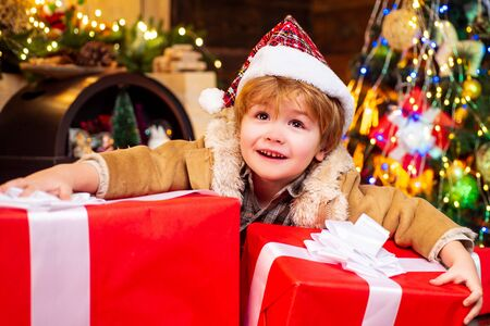 Cute little child is decorating the Christmas tree indoors. Happy little child dressed in winter clothing think about Santa near Christmas tree. New year concept.