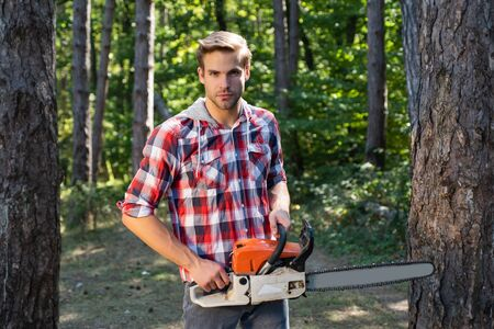 Strong lumberjack with an axe or chainsaw in a plaid shirt. Lumberjack on serious face carries chainsaw. Deforestation is a major cause of land degradation and destabilization of natural ecosystems.