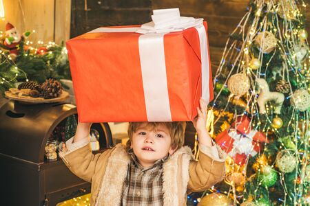 Christmas child holding a huge gift box. Happy child decorating Christmas tree. Happy cute child in Santa hat with present have a Christmas. New year Christmas concept.