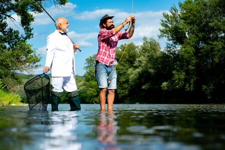 Men fishing in river during summer day. Still water trout fishing. Difference between fly fishing and regular fishing. Generations men. Stockfoto
