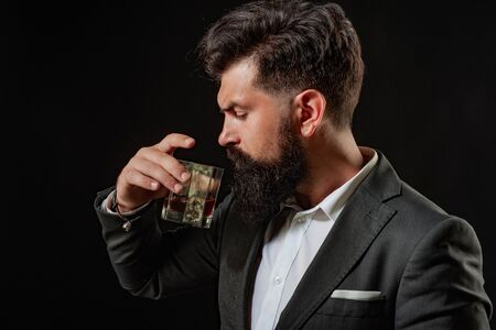 Man Bartender holding glass of whisky. Tasting and degustation concept. Retro vintage man with whiskey or scotch.